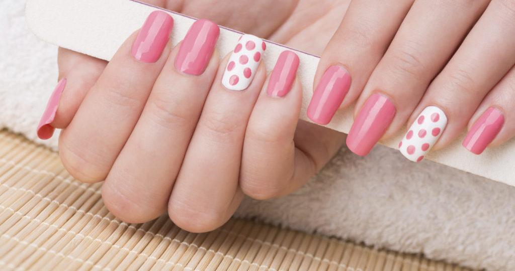 Beauty treatment photo of nice manicured woman fingernails holding nail file. Feminine nail art with nice pink and white nail polish.