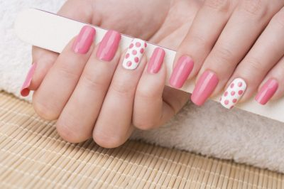 Beauty treatment photo of nice manicured woman fingernails holding nail file. Feminine nail art with nice pink and white nail polish.